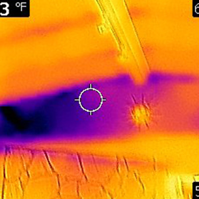 Infrared photo showing cold air (blue color in photo) entering the home near the cathedral ceiling due to missing insulation in the wall.